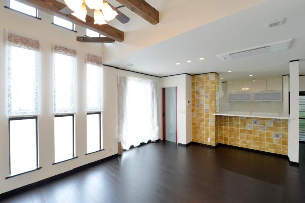 化粧針梁が見える勾配天井のリビングと、 その対面にあるキッチンの壁には、 アンティークタイルのデザイン貼りで、 明るいキッチンを演出。